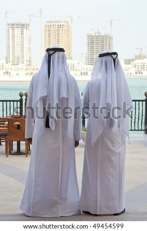 Two anonymous Arab men in traditional white clothing of dish dash and shemagh looking at the construction of new modern skyscrapers on the horizon