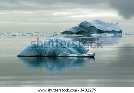 Two Antarctic icebergs in the Southern Ocean on a nearly flat sea. Picture was taken during a 3-month research expedition.