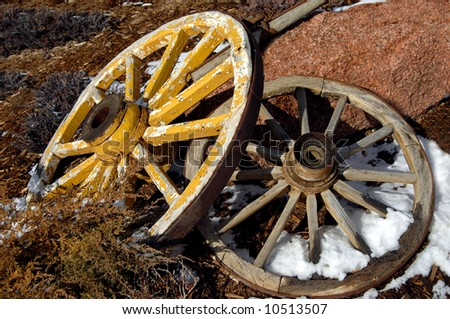 Two antique wagon wheels lay one on top of the other.  Yellow painted one is on top.  Bottom has snow between spokes.