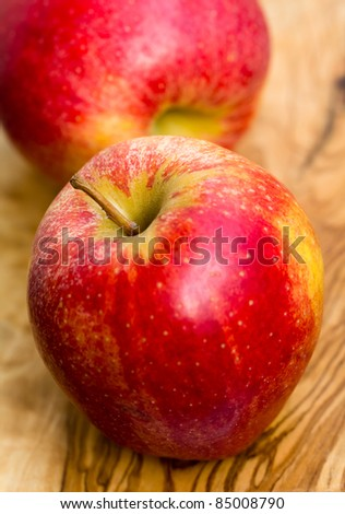 two apples on wooden table in garden