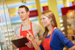 Two apprentices jointly check the inventory of a refrigerated section in the supermarket
