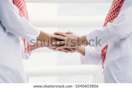 Two Arab young men are shaking hands to greet on the backdrop of a civilized city. #1040603806