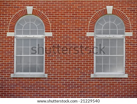 two arched windows on red brick building
