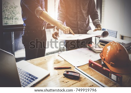 Two Architect man working with compasses and blueprints for architectural plan,engineer sketching a construction project concept. stock photo