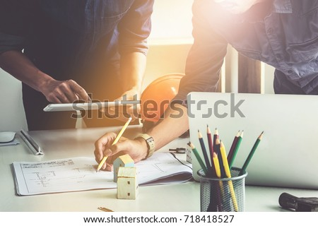 Two Architect woman working with compasses and blueprints for architectural plan,engineer sketching a construction project concept.