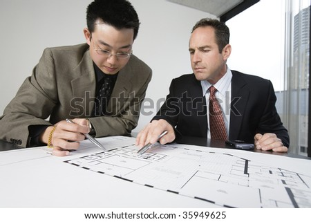 Two architects discussing on blueprints in an office.