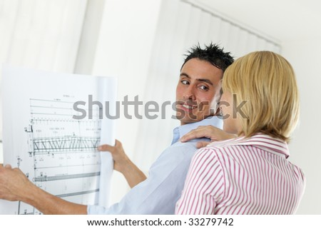 two architects examining blueprint indoors. Copy space