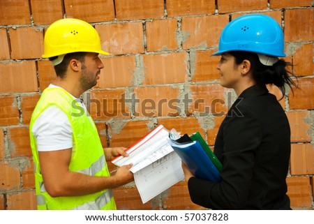 Two architects holding projects and  folders standing in profile and having a conversation on site - stock photo