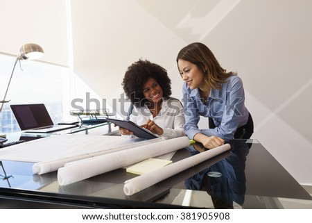 two architects in modern office building sitting on desk with blueprints and housing projects preview blueprints office desk preview save