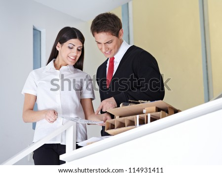 Two architects in the office discussing a construction drawing