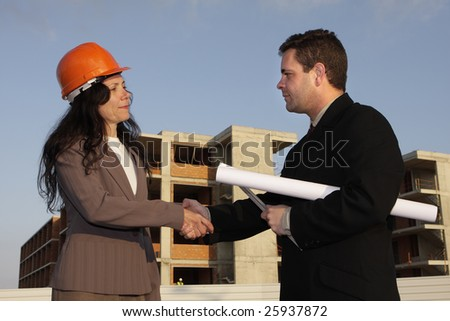 Two architects standing in front of a building site and shaking hands.