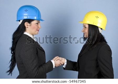 Two architects women in formal wear and wearing hard hat shaking their hands and make a deal