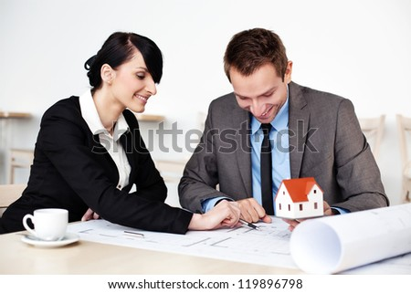 Two architects working sitting around table.