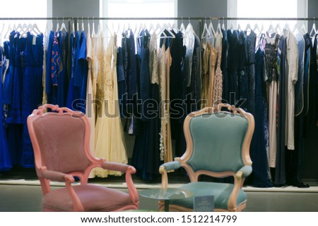 two armchairs and lots of clothes evening dresses at the stand great choice for the party