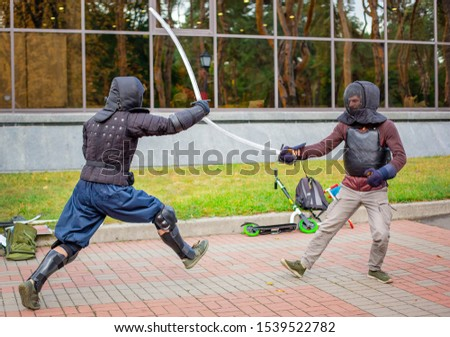 Two armed men lead a sword fight, a medieval fight, at a fun medieval tournament. Sports competitions. Gladiator fights.