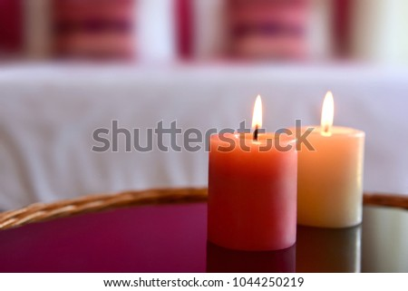 Two aromatic candles on a glass table. Bedroom interior. A cozy romantic atmosphere.  #1044250219