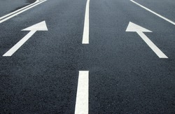 Two arrow signs on the road. White arrows on the asphalt. White forward arrows on a blurry street background