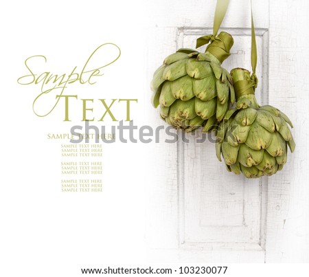 two artichokes hanging from a vintage door, area for copy space