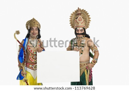 Two artists dressed-up as Rama and Ravana and holding a blank placard