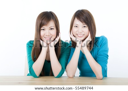 two asian adults sitting on a table and smiling