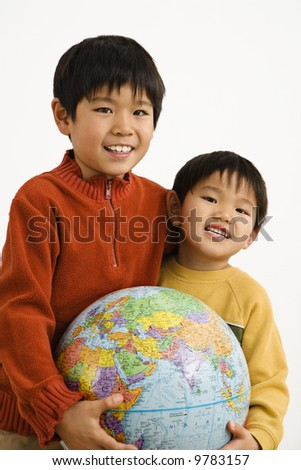 Two Asian boys holding world globe and smiling.