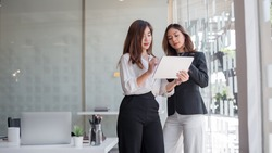 Two asian business woman work together to get the job done at the office.