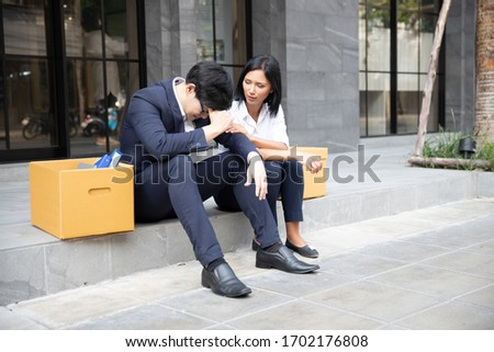 Two Asian businessman with cardboard box Sitting by the aisle. Unemployment crisis, corona virus covid-19 pandemic impact Asia Thailand. Business shutdown, Unemployed dismissed concept