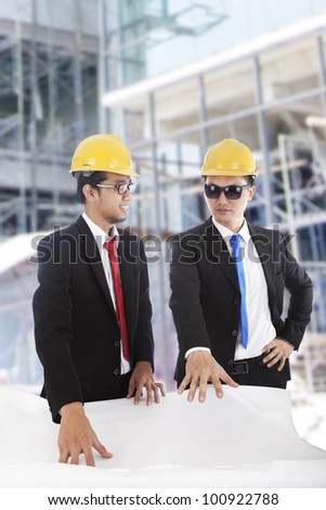 Two Asian businessmen discussing the blueprint at construction site