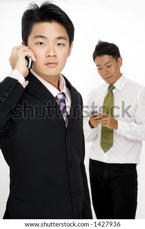 Two asian businessmen using their phones to communicate in different ways