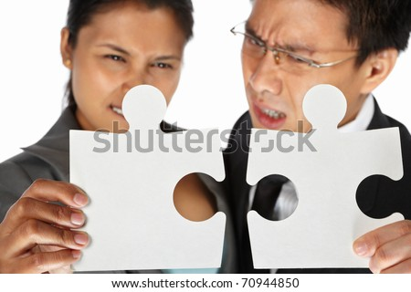 Two Asian businesspeople trying to connect the puzzle pieces