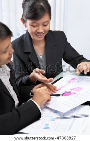 Two Asian businesswomen, South East Asian and Chinese discussing and teamwork concept - stock photo