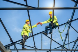 Two Asian construction workers wore safety clothing and safety harnesses to work on the steel roof structure.