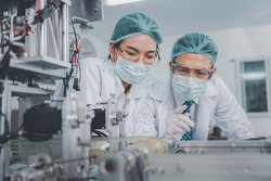 Two Asian doctor or engineer working at clean medical mask production factory, Production hygiene medical manufacturing qaulity inspection concept