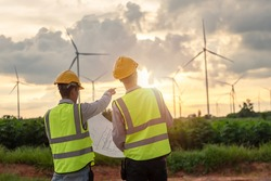 two asian engineers male checking wind turbines during beautiful sunset. Renewable energy technology and sustainability. Alternative energy for future