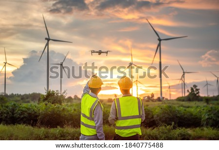 two asian engineers male flying drone surveying and checking wind turbines from the high angle view of the field during beautiful sunset. using drone technology for work. Alternative energy for future