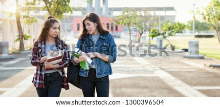 Two Asian female students discussing about latest content of textbook in park at university after learning in classroom. Life of studying and friendship concept.