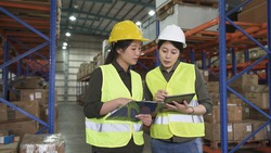 two asian female worker colleagues holding clipboard and digital pad and discussing new project in large stockroom