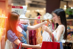 two asian girls enjoy shopping together in department store.