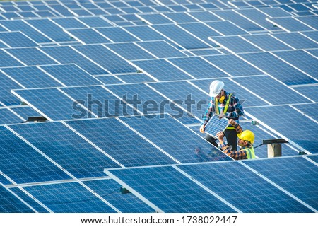 Two Asian male engineering teams are about to install solar panels. At the solar power generating station Asian engineering team ordered and installed solar cells