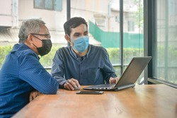 Two Asian man meeting business by laptop computer in cafe, Two people wear face mask prevent coronavirus covid19