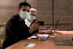 Two Asian men discussing his camera and photography. Under the conditions of protection against COVID 19 by wearing a protective mask.