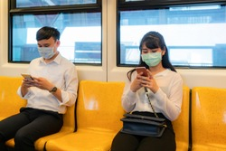 Two Asian people wearing mask sitting in subway distance for one seat from other people keep distance protect from COVID-19 viruses and people social distancing  for infection risk