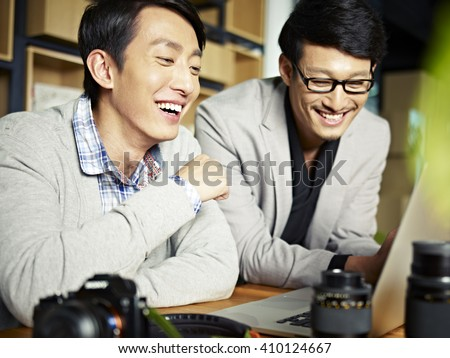 two asian photographers working together selecting images using laptop computer, happy and laughing.