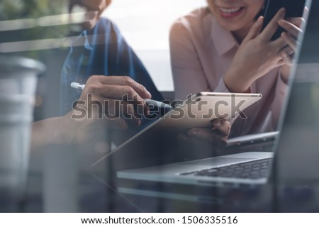 Two asian startup business colleagues using digital tablet, together working on laptop computer. Smiling coworkers making great business discussion in modern coworking office