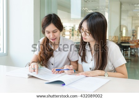 Two Asian students studying together at university.