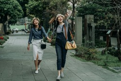 two asian travelers women walking in old town street pointing away to hotel destination in tokyo japan. full length young girls running holding hands excited sharing looking in walkway japanese style