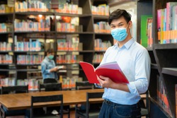Two Asian university students wearing face mask and standing in library social distance from other 6 feets to avoid the spread of coronavirus in University.
