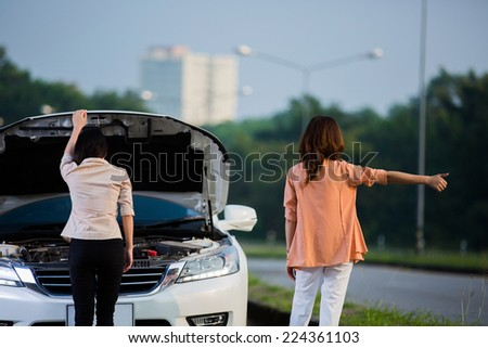 Two Asian women are doing a breakdown on the road stance to the car park