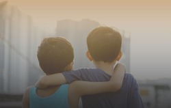 Two asian young brothers hugging each others over the sunset. Brotherhood friendship concept. Vintage editing