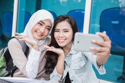 two asian young student taking selfie together with smartphone on campus